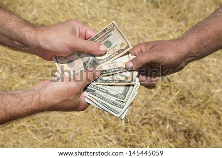 Farmer and buyer hands holding dollar banknote in field
