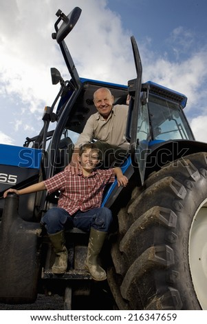 Farmer and grandson leaning out of tractor