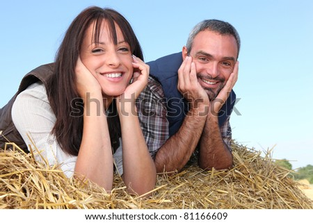Farmer and wife laying in hay - stock photo