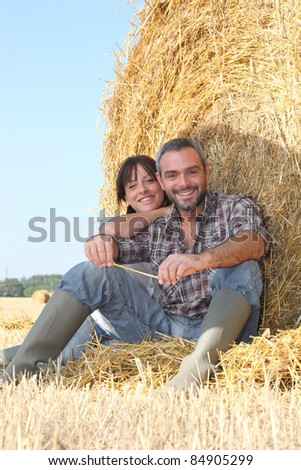 Farmer and wife sat on hay bale - stock photo