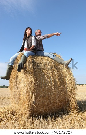 Farmer and wife sat on hay roll - stock photo