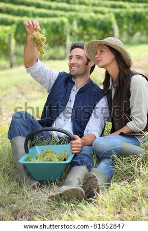 Farmer and wife sat with basket of grapes - stock photo