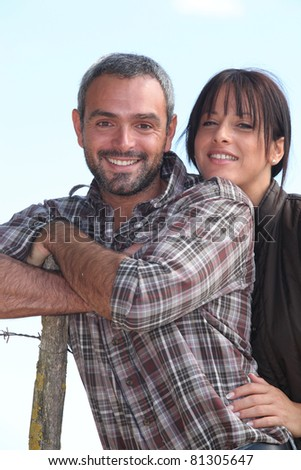 Farmer and wife stood outdoors by fence - stock photo