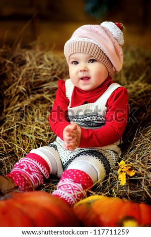 farmer baby girl in fashion clothes sitting on a hay with pumpkin - stock photo