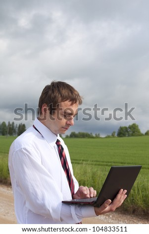 Farmer calculating earning in field. - stock photo