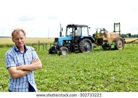 Farmer checking soybean field. The unique technology of growing crops. Farmer sitting in the field on a background of wheat and soybeans. Golf bread. Growing non-GMO soybeans. Eco friendly product.1 - stock photo