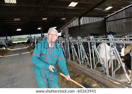 Farmer cleaning barn - stock photo