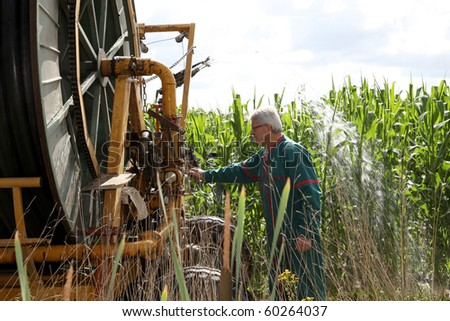 Farmer controlling irrigation machinery - stock photo