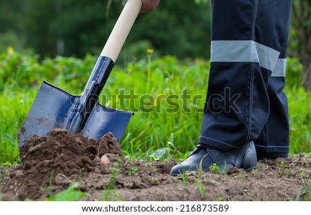 Farmer digging a garden - closeup shot - stock photo