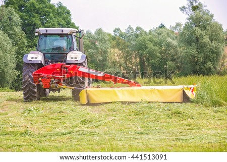 Farmer driving a tractor on the field with the attached tool used to cut grass on the field where it will dry - stock photo