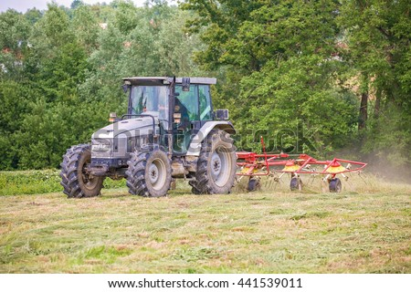 Farmer driving a tractor on the field with the attached tool used to spread hay on the field where it will dry
