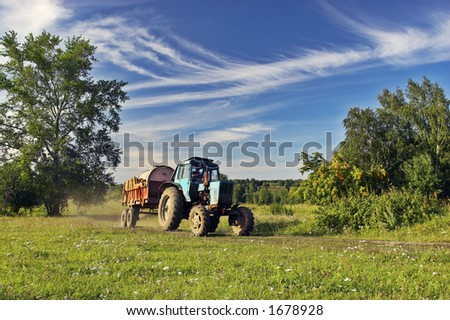 Farmer driving tractor - stock photo