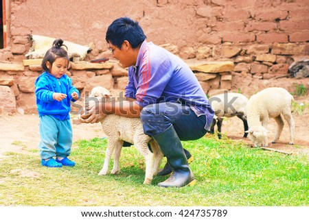 Farmer father with his daughter and sheep - stock photo