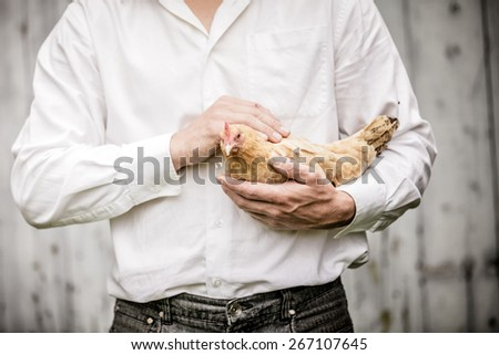 Farmer Holding a Beige Chicken in front of the Farm - stock photo
