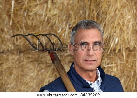 Farmer holding a pitchfork - stock photo