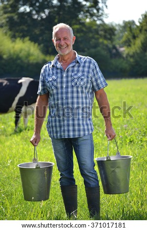 Farmer holding buckets after milking cow. - stock photo