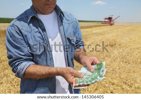Farmer holding Euro banknote with combine harvester in background - stock photo