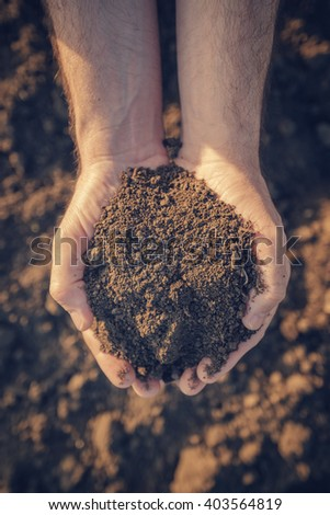 Farmer holding pile of arable soil and examining its quality on fertile agricultural land, male agronomist preparing land for new seeding season, close up of hands. - stock photo
