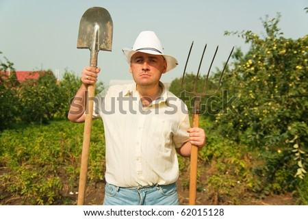 farmer holding pitchfork and spade standing in a field - stock photo