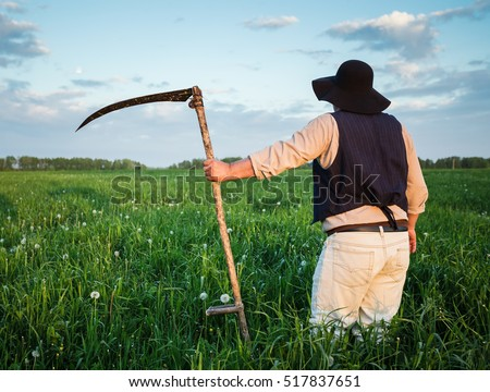 Farmer in a hat  and with a scythe on green field