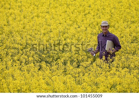 Farmer in a rapeseed field with his laptop - stock photo
