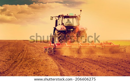 Farmer in tractor preparing land for sowing, photo manipulated to achieve old cross processing xpro look. - stock photo