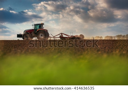 Farmer in tractor preparing land with seedbed cultivator, sunset shot - stock photo