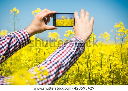Farmer inspect quality of canola field and taking photo with mobile phone - stock photo