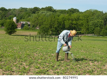 farmer irrigating his crop with a watering can - stock photo
