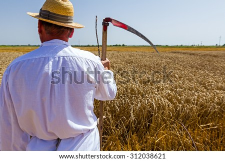Farmer is holding scythe in front of field with mature wheat. - stock photo