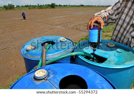 farmer mix pesticide on the rice field - stock photo