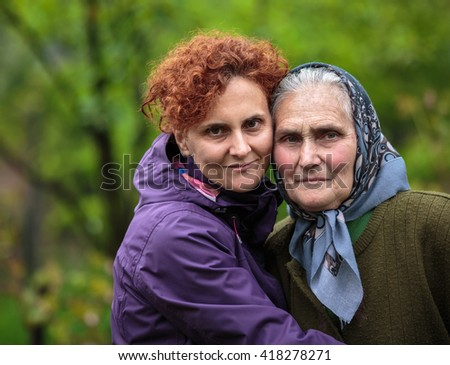 Farmer mother and daughter outdoor, closeup portrait - stock photo