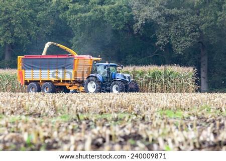 Farmer on tractor harvesting corn - stock photo