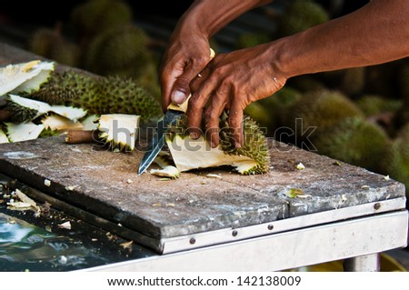 farmer peel a durian in the orchard - stock photo