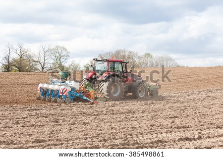 Farmer planting and seeding the spring crop with a five row agricultural planter in a newly ploughed , or plowed, field - stock photo