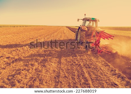 Farmer plowing stubble field with red tractor, photo manipulated to achieve old cross processing xpro look. - stock photo