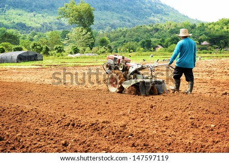 Farmer plowing the field. Cultivating tractor in the field - stock photo