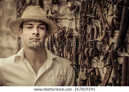 Farmer Portrait in front of a Wall Full with Old Rusty Tools - stock photo