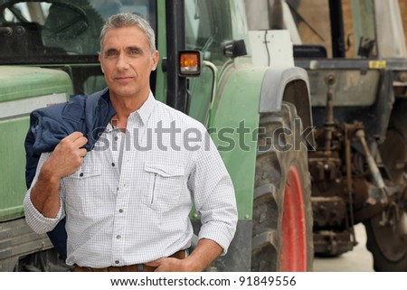 farmer posing in front of his tractor - stock photo