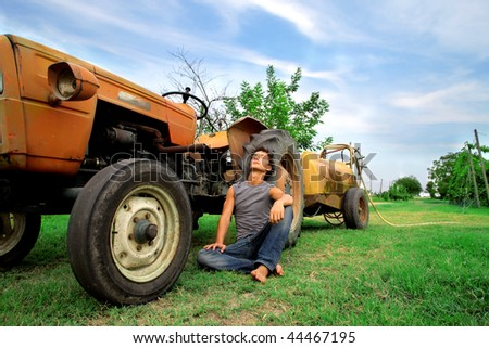 farmer resting against tractor - stock photo