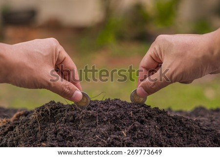 Farmer's hand planting coin in soil - stock photo