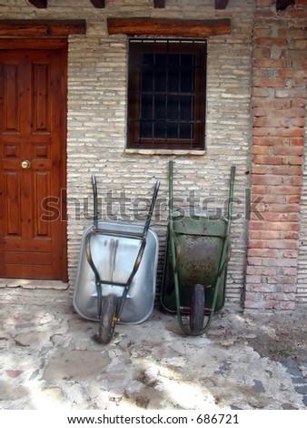Farmer's wheelbarrows lying on a farm house wall - stock photo