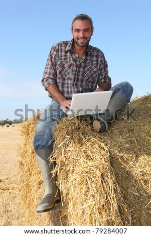 farmer seated on straw bale and doing computer - stock photo