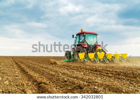 Farmer seeding crops at field - stock photo