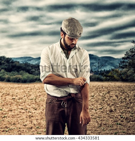 Farmer shortens his sleeves in the field. - stock photo