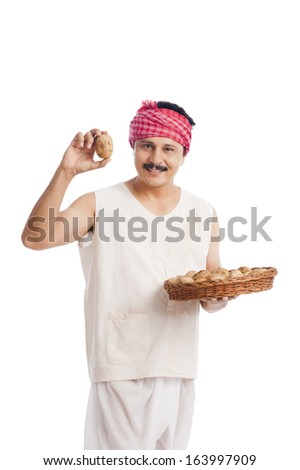 Farmer showing a potato and smiling - stock photo