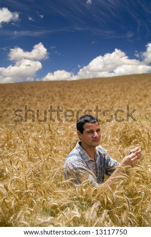 farmer sitting in a wheat field - stock photo