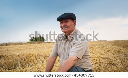 Farmer sitting in the field, waiting for his crop - stock photo