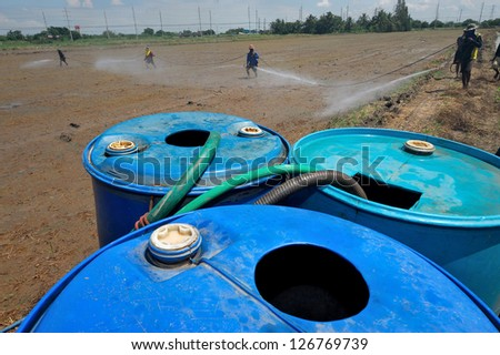 farmer spary pesticide on the rice field - stock photo