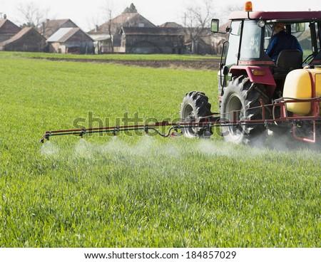 Farmer spraying wheat field with tractor sprayer at spring season - stock photo